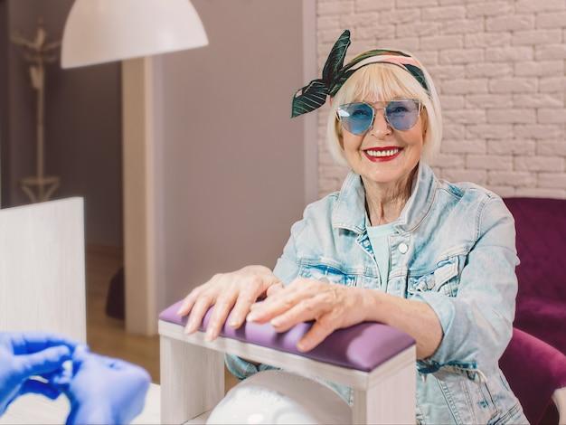Пожилая стильная старшая женщина в синих солнцезащитных очках и джинсовой куртке в салоне-студии счастлива