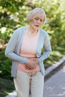 Elderly upset involved woman touching her belly and expressing negative emotions while suffering from stomachache outdoors