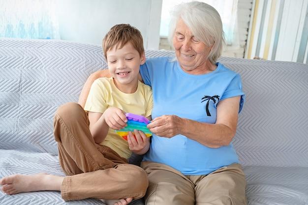 노인 백발 백인 여자가 소년과 함께 소파에 앉아 아이의 장난감을 들고 웃고있다.
