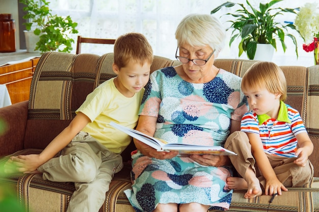 An elderly, white-haired woman with glasses is sitting on a sofa with two small boys and holding an open book in her lap. a grandmother reads a fairy tale to her grandchildren.