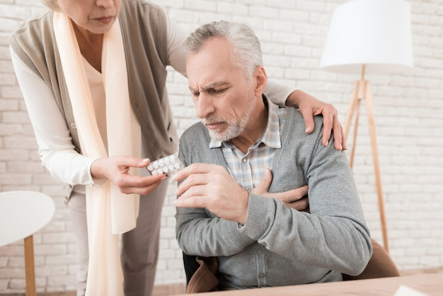 Elderly wife gives pills to sick old husband.
