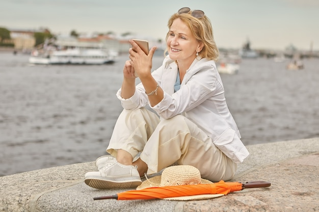 Elderly woman about 60 years old is sitting near river in casual and elegant cloth with smartphone in hands in saint-petersburg.