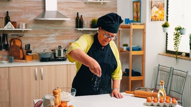 Пожилая женщина добавляет муку на стол вручную, сидя на домашней кухне. старший пекарь на пенсии с косточкой и равномерным обсыпанием, просеиванием, разложением ингредиентов для выпечки домашней пиццы и хлеба.