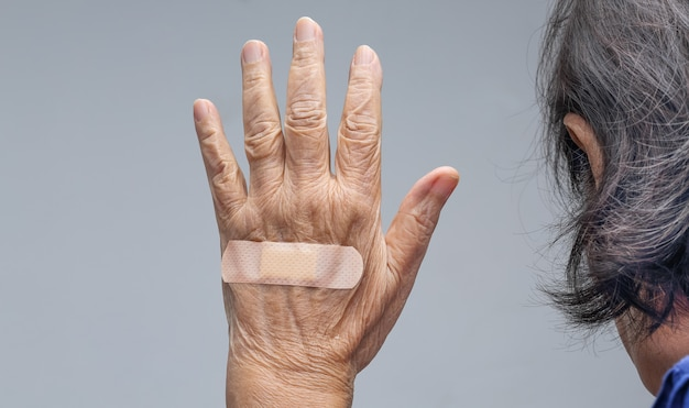Elderly woman adhesive bandage on her hand