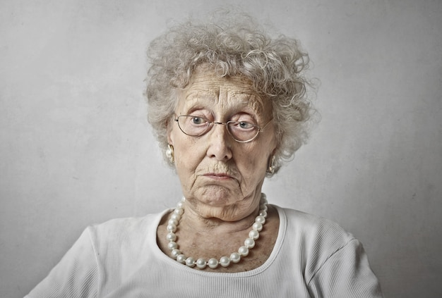 Elderly woman against a white wall with a blank stare