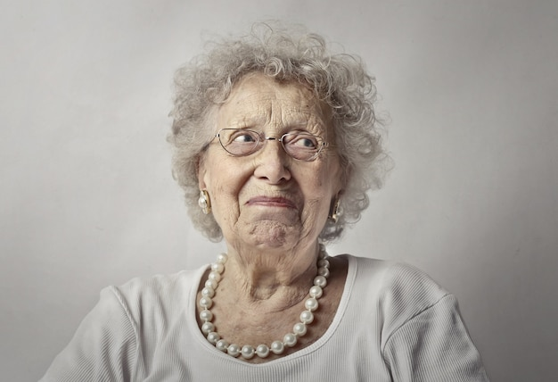 Elderly woman against a white wall with a worried look on her face