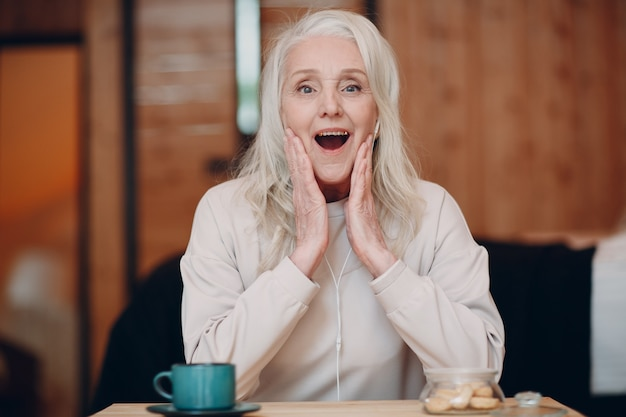 Elderly woman amazed with headphones talking video call on laptop in kitchen waving at screen chatting