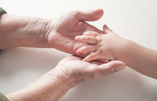 Пожилая женщина и ребенок руки вместе.