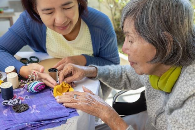 Пожилая женщина и дочь занимаются трудотерапией рукоделия от болезни альцгеймера или деменции