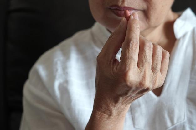 Пожилая женщина ест лекарства и с таблетками и стаканом воды в домашних условиях