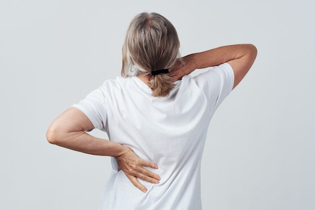 Elderly woman back pain back view health problems