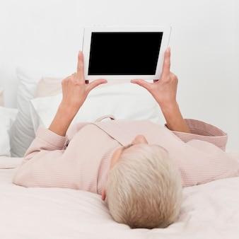 Elderly woman in bathrobe looking at tablet in bed