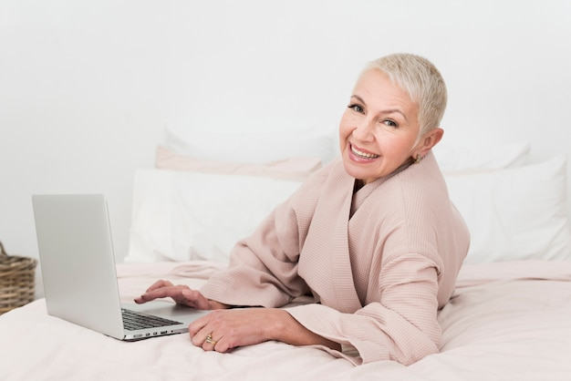 Elderly woman in bathrobe smiling and posing with laptop in bed