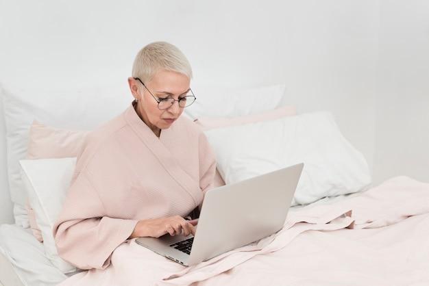 Elderly woman in bathrobe working on laptop in bed