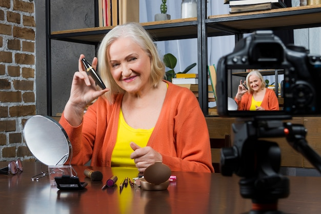 Elderly woman blogger recording her doing make up online video by camera,
