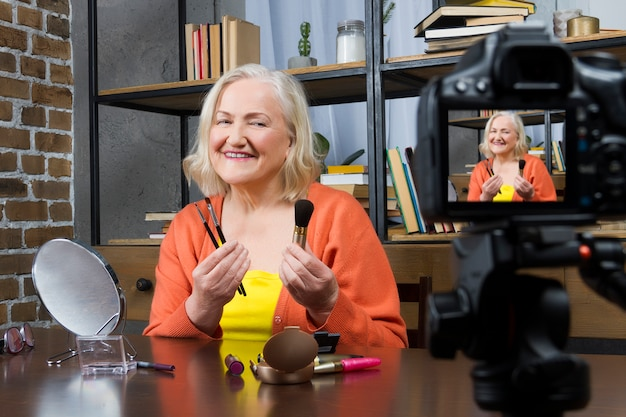 Elderly woman blogger recording her doing make up online video by camera