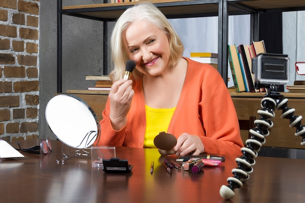 Elderly woman blogger recording her doing make up online
