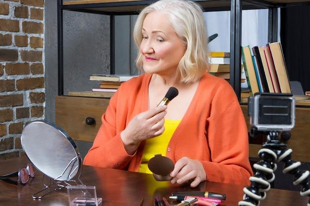 Elderly woman blogger recording her doing make up online