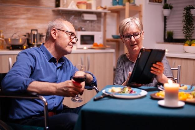 Пожилая женщина просматривает на планшетном пк и муж-инвалид в инвалидной коляске, держа бокал. иммобилизованный старший муж-инвалид просматривает по телефону телефон, наслаждаясь праздничным мужчиной, выпивая стакан красного вина