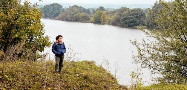 秋の川辺で歩きながらお年寄りの女性