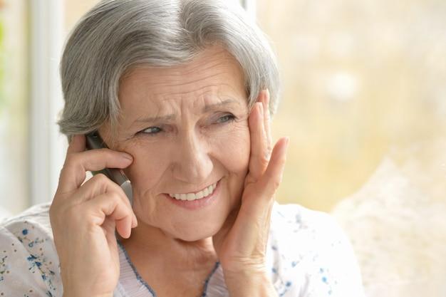 집에서 전화를 거는 할머니