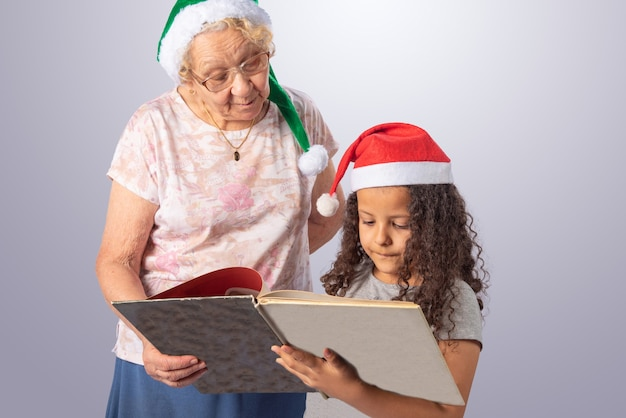 Elderly woman and child with christmas hat reading a book on gray