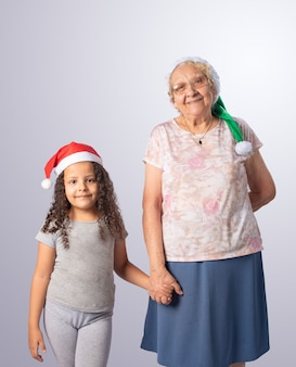 Elderly woman and child with christmas hat together on gray