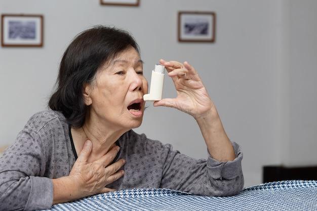 질식하고 천식 스프레이를 들고 할머니