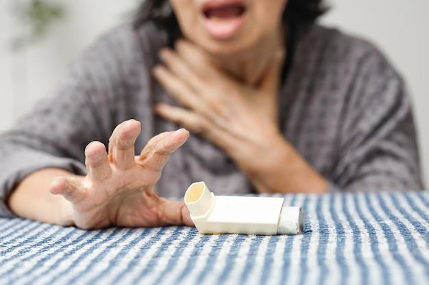喘息スプレーを窒息させて保持している年配の女性