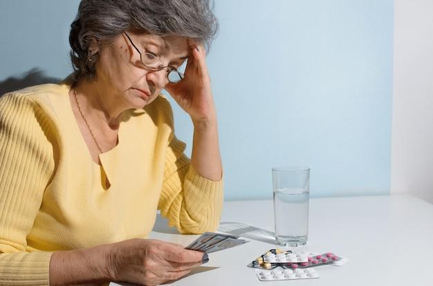 治療のためにお金を数える年配の女性。薬を持ってテーブルの台所に座っている年金受給者。