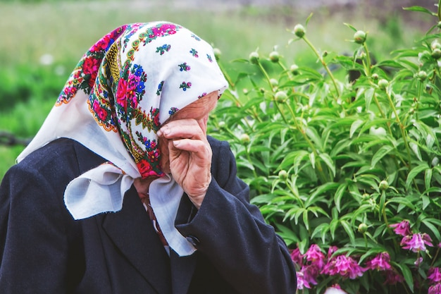 An elderly woman cries wiping her tears with her hand