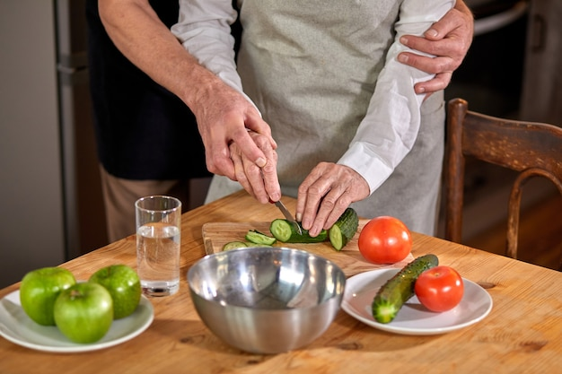 Elderly woman cutting a cucumber for a salad in a modern, eco kitchen, preparing food with her husband hugging her from back. at home. cropped people
