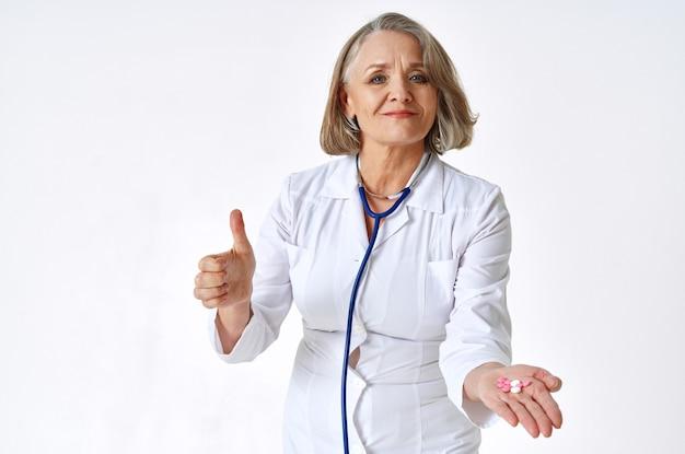 Пожилая женщина-врач в стетоскопе медицины белого халата