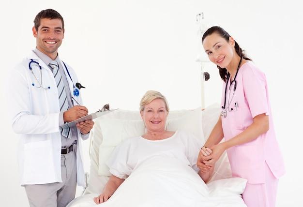 Elderly woman between doctor and nurse