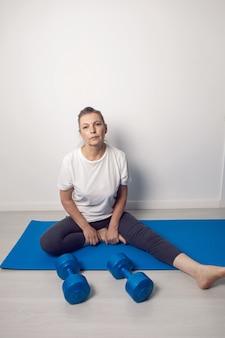 Пожилая женщина занимается йогой на синем коврике с гантелями в белой комнате дома