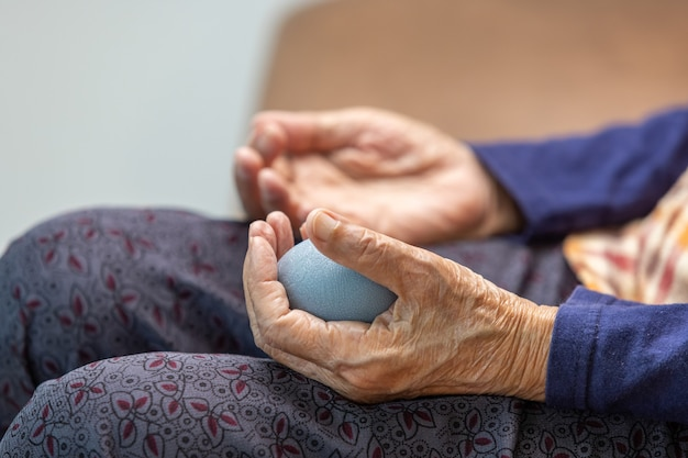Elderly woman doing rubber ball for exercise fingers, palm ,hand and foot muscle with caregiver take care.