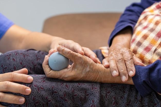 Пожилая женщина делает резиновый мяч для упражнений, пальцы, ладони, руки и мышцы стопы с опекуном.