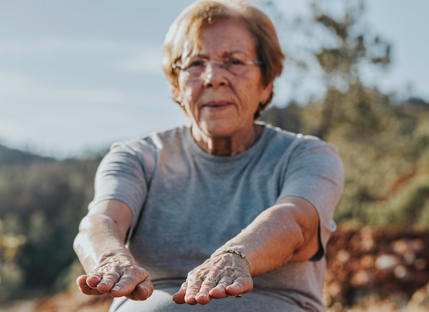 Elderly woman doing their stretches in the park with selective focus in the fingers