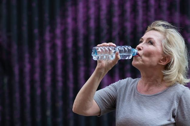 Пожилая женщина пьет воду в бутылках после тренировки