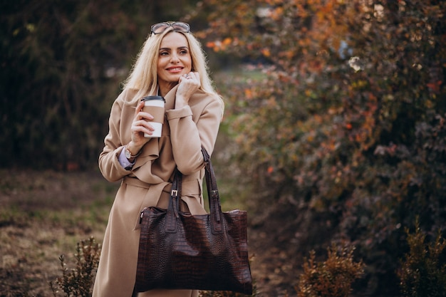 Elderly woman drinking coffee outside the autumn park