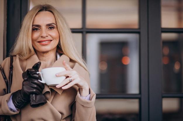 Пожилая женщина пьет кофе у кафе