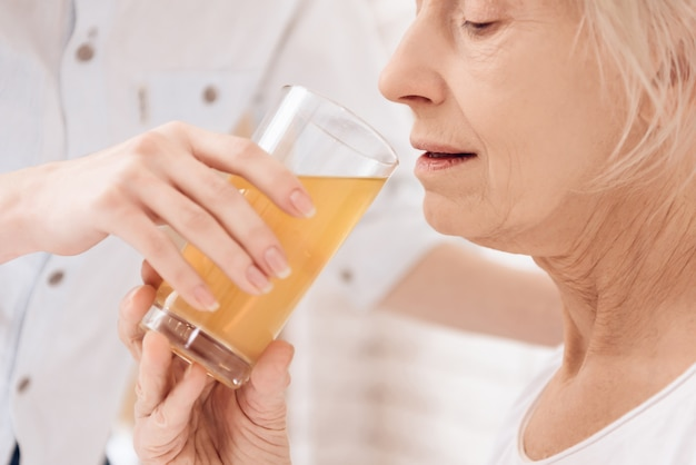 Elderly woman drinking juice in hospital.