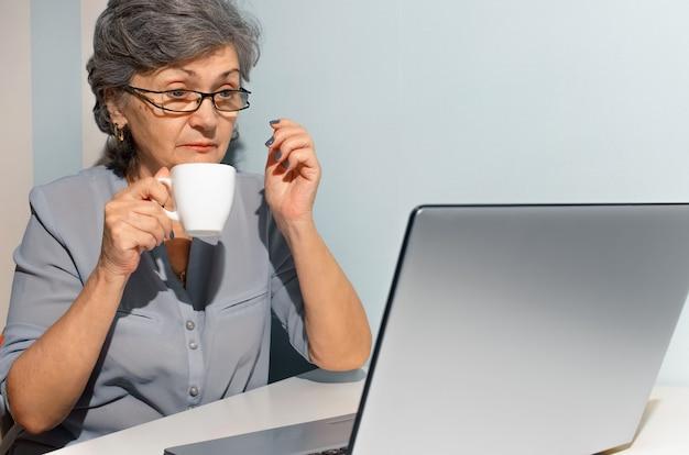 Пожилая женщина пьет кофе и удивленно смотрит на ноутбук.