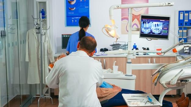 歯科医院で男性歯科医と診察中の年配の女性。歯科矯正医が、看護師が手術用の道具を準備している間、口腔病学の椅子に座っている患者に話しかけます。