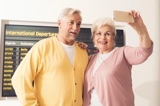 A elderly woman and an elderly man make a photo