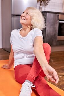 Пожилая женщина занимается спортом на полу дома, сидит со скрещенными ногами и смотрит вверх, улыбаясь