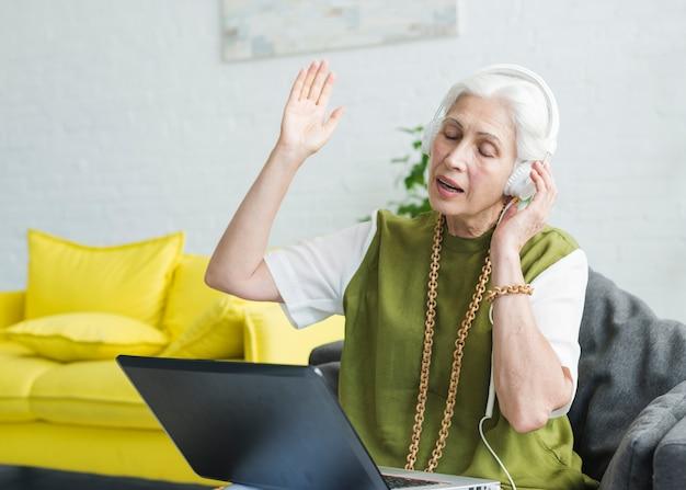 An elderly woman enjoying music on headphone attach on laptop