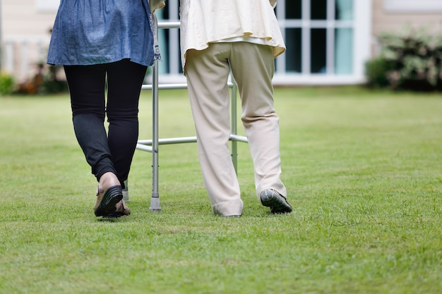 Elderly woman exercise walking in backyard with daughter