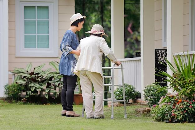 年配の女性が娘と一緒に裏庭を歩く運動