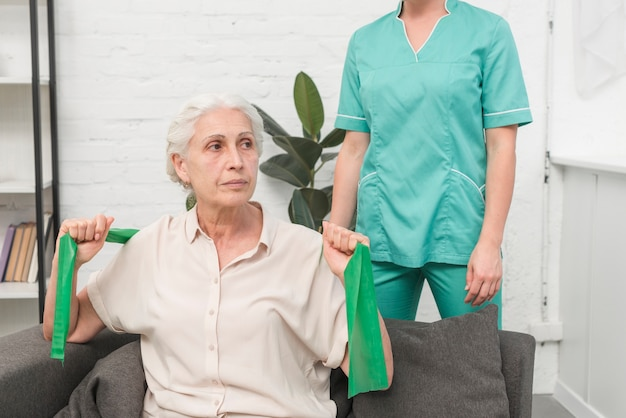 Elderly woman exercising with green stretch band sitting in front of female nurse